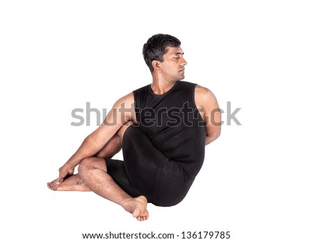 Yoga ardha matsyendrasana half spinal twist pose by Indian man in black costume isolated at white background. Free space for text - stock photo