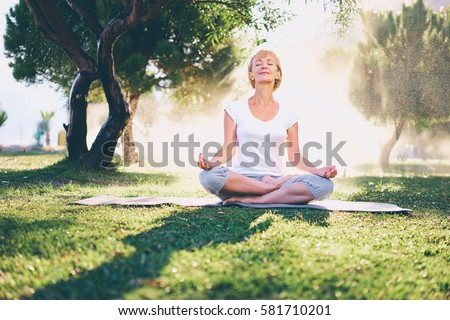 Yoga at park. Senior woman in lotus pose sitting on green grass. Concept of calm and meditation.
