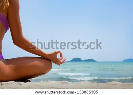 yoga background, woman in lotus position meditating on the beach - stock photo