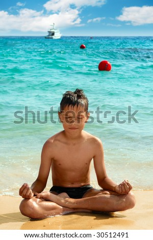 Yoga boy are sitting in lotus position - stock photo