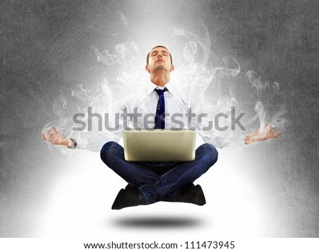 yoga businessman in total concentration with laptop - stock photo
