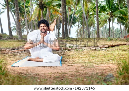 Yoga by happy Indian man in white trousers near palm trees in Kerala, India - stock photo