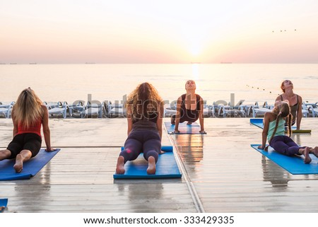 yoga class - group of people practicing yoga during sunrise - stock photo