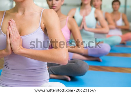 Yoga class in lotus pose in fitness studio at the leisure center - stock photo