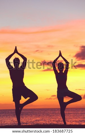 Yoga couple training in sunset in tree pose meditating outdoors by beach ocean sea. Man and woman working out training in serene ocean landscape. Silhouette against sunset - stock photo