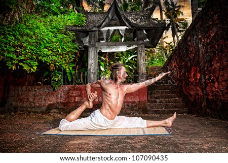 Yoga eka pada raja kapotasana by fit man in white trousers near stone temple in tropical forest - stock photo