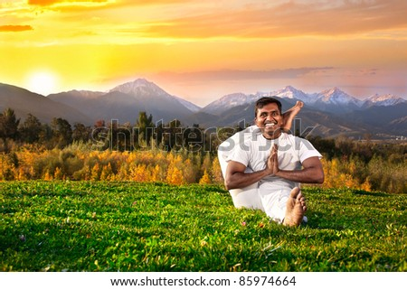 Yoga eka pada shirasana foot behind the head pose by happy Indian Man in white cloth in the morning at mountain and sunset sky background - stock photo