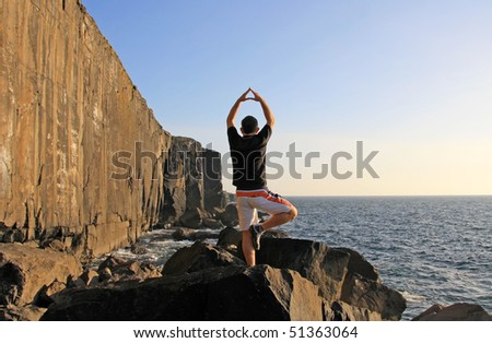 Yoga exercise on the cliffs - stock photo