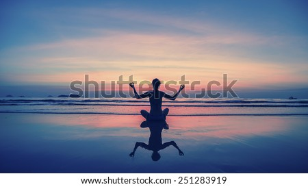 Yoga, fitness, healthy lifestyle. Silhouette meditation girl on the background of the stunning sea and sunset. - stock photo