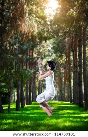 Yoga garudasana eagle pose by woman in white costume on green grass in the park around pine trees - stock photo