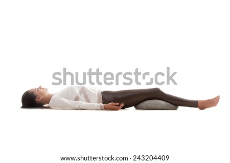 Yoga girl on white background lying in Shavasana (Savasana, Corpse Pose) - stock photo