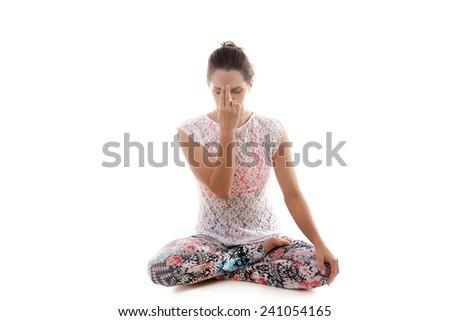 Yoga girl on white background practicing nadi shodhana pranayama (Alternate, Nostril, Breathing) - stock photo
