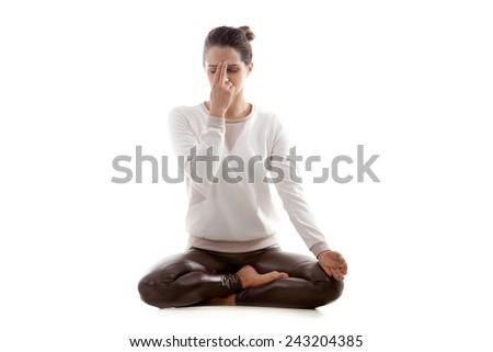 Yoga girl on white background practicing nadi shodhana pranayama (Alternate, Nostril, Breathing) in lotus pose - stock photo