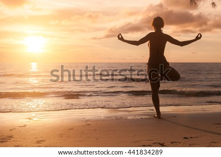 Yoga girl silhouette on beautiful sunset on the sea.