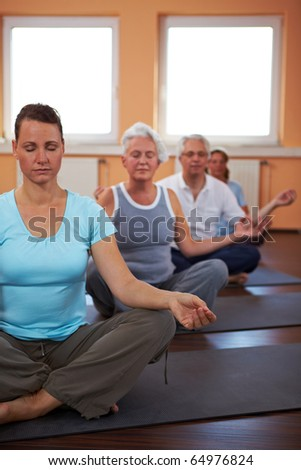 Yoga group in gym doing meditation exercises