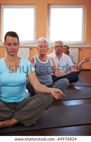 Yoga group in gym doing meditation exercises - stock photo