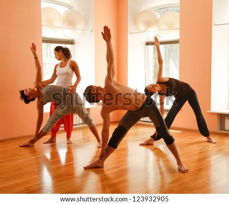 Yoga group practicing under instructors guidance - stock photo