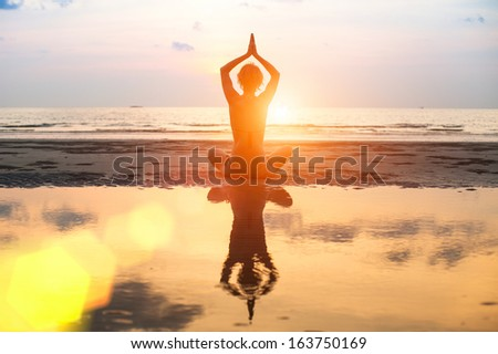 Yoga, harmony of health, silhouette young woman on the beach at sunset. - stock photo