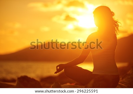 yoga in the beach. woman meditating in lotus pose on the beach at sunset - stock photo