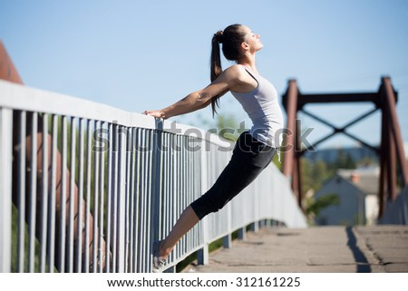 Yoga in the city: beautiful sporty teenage girl working out on the old bridge on summer day, doing backbend on railing, warming up muscles, breathing fresh air - stock photo