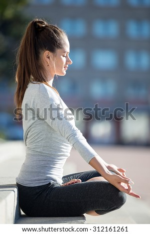 Yoga in the city: beautiful young fit woman wearing sportswear meditating, breathing, sitting with crossed legs in Half Lotus Posture on the street on summer day, Ardha Padmasana, full length - stock photo