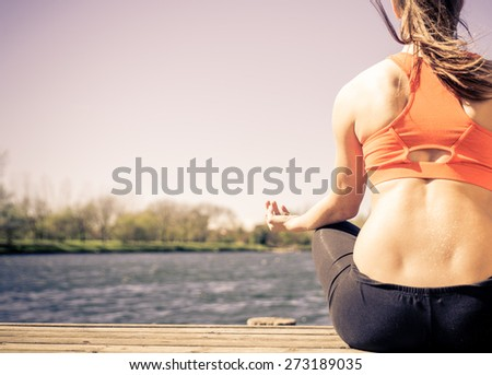 yoga in the nature. woman making yoga exercises in front of the lake. concept about relaxation, meditation, fitness and people - stock photo