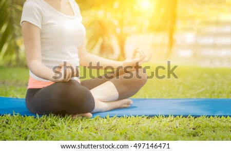 Yoga in the park beside lake, outdoor with effect light, healthy woman.  Concept of healthy lifestyle and relaxation.