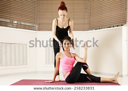 Yoga instructor corrects student's head while exercising yoga - stock photo