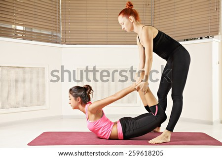 Yoga instructor helping brunette in back bend pose - stock photo