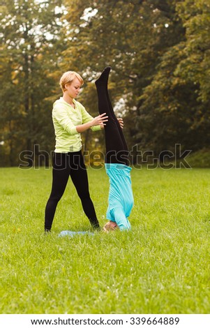 Yoga instructor is showing a woman how to do correct Headstand. Yoga class - stock photo