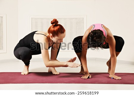 Yoga instructor shows to student how to stay on hand - stock photo