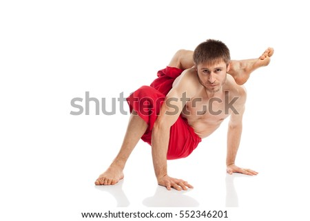 Yoga man doing exercises in studio at white background
