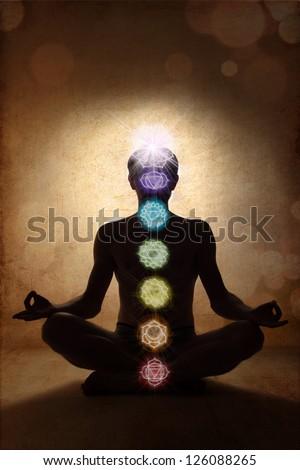 Yoga man in lotus pose with chakra symbols - stock photo