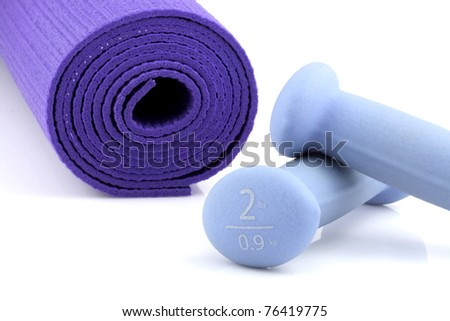 yoga mat and set of two pounds women dumbbell weights. - stock photo