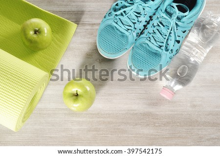 yoga mat with sport shoes and healthy food on a wooden background