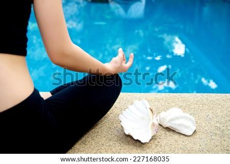 Yoga Meditation hand by pool, lotus pose (padmasana) - stock photo
