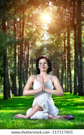 Yoga meditation in gomukhasana pose by woman in white costume on green grass in the park around pine trees