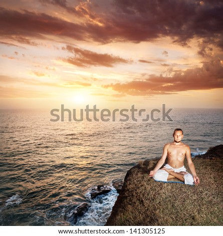 Yoga meditation in lotus pose by man in white trousers on the cliff near the ocean at sunset in Kerala, India - stock photo
