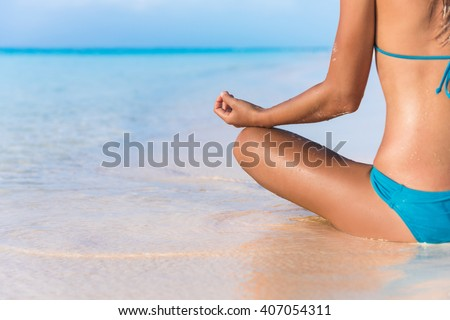 Yoga meditation on beach. Bikini body woman meditating relaxing sitting in water in tropical summer travel. Closeup on hand. Health and fitness retreat concept. - stock photo