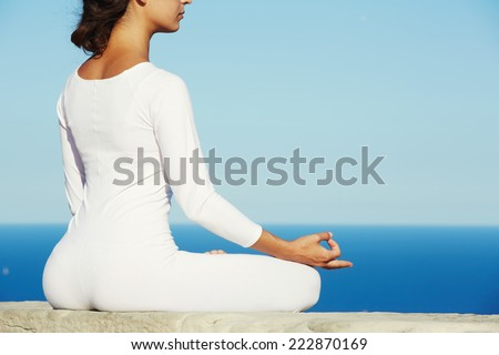 Yoga meditation on high altitude with blue sea on background, woman meditating yoga enjoying sunny evening, meditating woman, beautiful woman in white clothes seated in yoga pose outdoors - stock photo