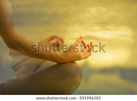 Yoga meditation peace, soul and mind zen balance concept. Young female in yoga posture meditating and making a zen symbol with her hands with beautiful sunset background. - stock photo