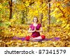Yoga meditation pose by concentrate beautiful woman in red cloth and yellow leaves around in the autumn - stock photo