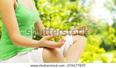 Yoga Meditation, Sitting Outdoors in Lotus Pose, Woman Meditating Hand over Green Unfocused Park - stock photo