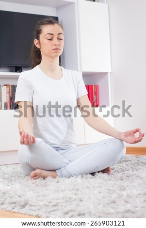 Yoga Meditation Woman Relaxing at home.Healthy Lifestyle in Lotus Posture .Caucasian female meditate on the floor. - stock photo