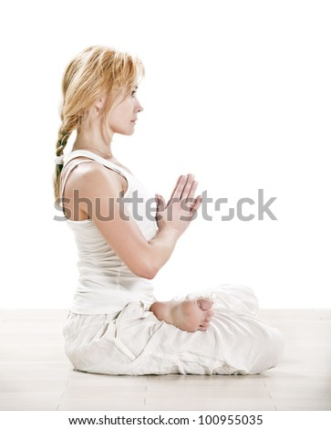 Yoga meditative padmasana lotus pose by beautiful young Caucasian woman in white - stock photo