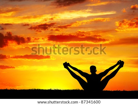 Yoga merudandasana balancing bear pose by Man in silhouette with orange sunset sky background. Free space for text - stock photo