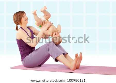 Yoga / Mother with her baby doing yoga exercise.