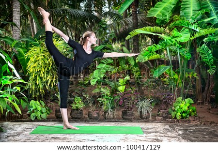 Yoga Natarajasana dancer balancing pose by woman in black cloth in the garden with palms, banana trees and plants in the pots - stock photo