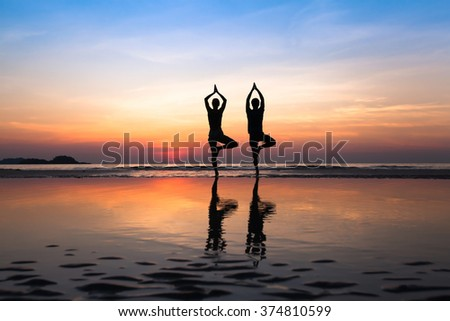 yoga on the beach, group of people practicing healthy lifestyle - stock photo