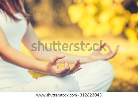Yoga outdoors in warm autumn park. Woman sits in lotus position zen gesturing. Concept of healthy lifestyle and relaxation - stock photo